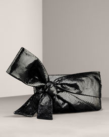 Fashionable and functional, this statement making bow turns this traditional evening clutch into an of-the-moment wristlet. Black python skin. Oversized bow can be used as a wristlet. 100% satin li
