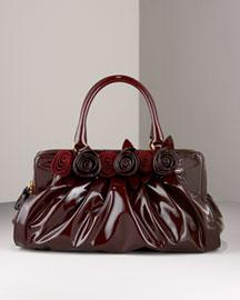• Wine (dark red) leather. • Framed top; zip closure. • Top handles. • Gold-tone hardware. • Rosette appliqués. • 7