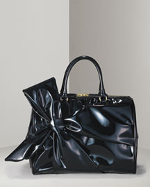 Black lacca. Oversized bow on side. Top handles with rings. Gold-tone hardware. Double zip closure. 10 1/2